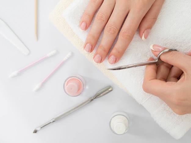 Płaskie ręce świeckich kobiety za pomocą nożyczek do paznokci