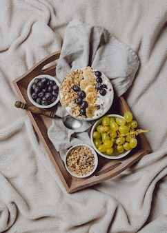 Płaskie śniadanie w łóżku z płatkami i bananem