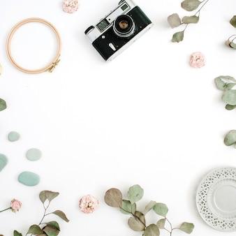 Płaskie świecące ramki z aparatem retro, gałęzie eukaliptusa, płyta na białym tle