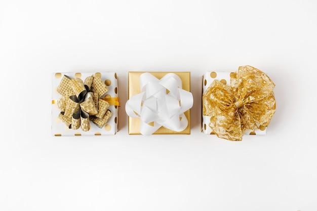 Płaskie świeckich boże narodzenie lub tło strony z pudełka i dekoracje w kolorach złota. płaski układanie, widok z góry