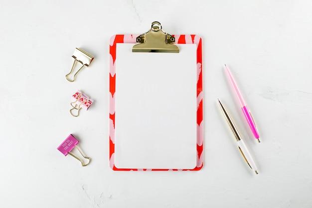 Płaskie świeckich moda biuro domowe obszar roboczy z pustego schowka papieru, długopisy i klipy na tle biały stół. widok z góry. kopia przestrzeń.