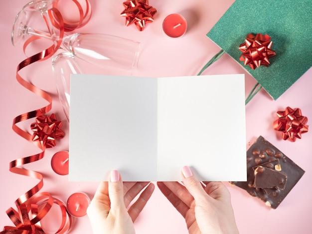 Płaskie świeckich ręce kobiety trzymać białą otwartą pustą pocztówkę na tle dekoracji świątecznych.