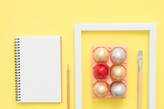 Płaskie świeckich widok z góry kolorowe pisanki malowane w pastelowych kolorach składu i makiety puste notatnik