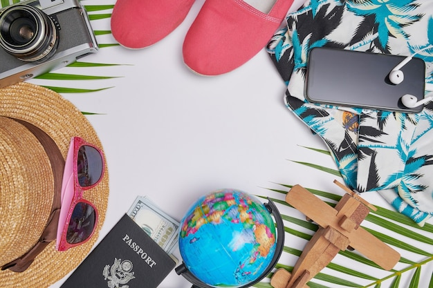 Płaskie świeckie akcesoria podróżne na białym tle z liściem palmowym, aparatem, kapeluszem, paszportami, pieniędzmi, hawajami, butami, telefonem, globusem i okularami przeciwsłonecznymi. widok z góry, koncepcja podróży lub wakacji. lato w tle.