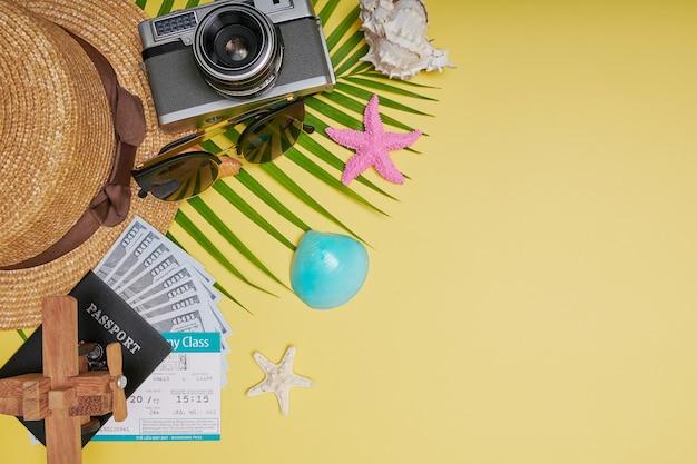 Płaskie świeckie akcesoria podróżne na żółtym tle z liściem palmowym, aparatem, butem, kapeluszem, paszportami, pieniędzmi, biletami lotniczymi, samolotami i okularami przeciwsłonecznymi. widok z góry, koncepcja podróży lub wakacji. lato w tle.