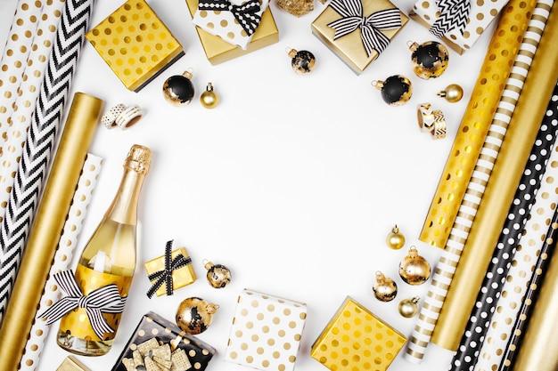 Płaskie świeckie boże narodzenie lub tło strony z pudełkami prezentowymi, butelką szampana, kokardkami, dekoracjami i papierem do pakowania w kolorach złotym i czarnym. płaski układanie, widok z góry