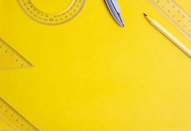 Płaskie świeckie linijki, kompasy i ołówek na żółtym tle, kopia przestrzeń