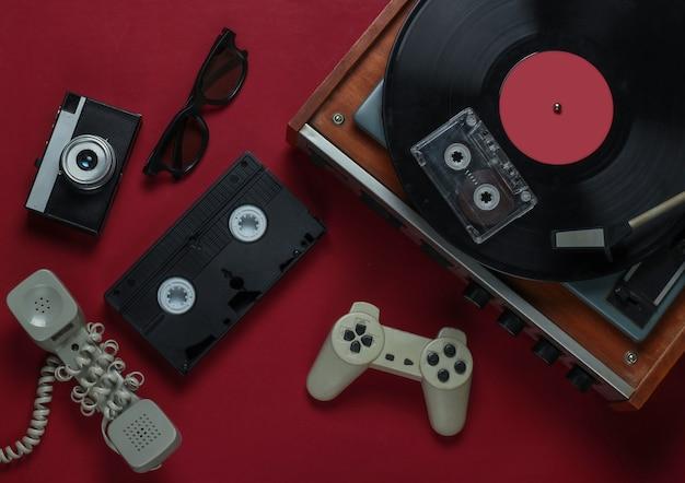 Płaskie świeckie media i rozrywka w stylu retro. gramofon z płytą winylową, kamerą filmową, kasetą wideo, kasetą audio, gamepadem, słuchawką na czerwonym tle. 80s. widok z góry