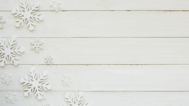 Płaskie świeckie świąteczne ozdobne płatki śniegu na drewnianej desce