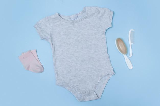 Płaskie, szare body niemowlęce na niebieskiej powierzchni