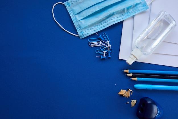 Płaskie szkoły świeckie po pandemii koronawirusa, powrót do szkoły w nowej rzeczywistości, przybory szkolne, maska ochronna i środek antyseptyczny na niebieskim tle