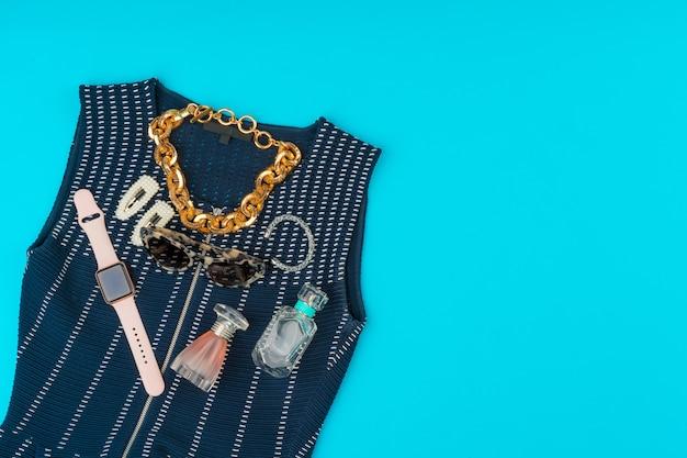 Płaskie ubrania modnej kobiety na niebieskim tle