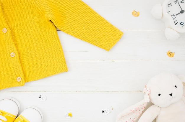 Płaskie ubrania świeckich dziecka z drewnianym tłem