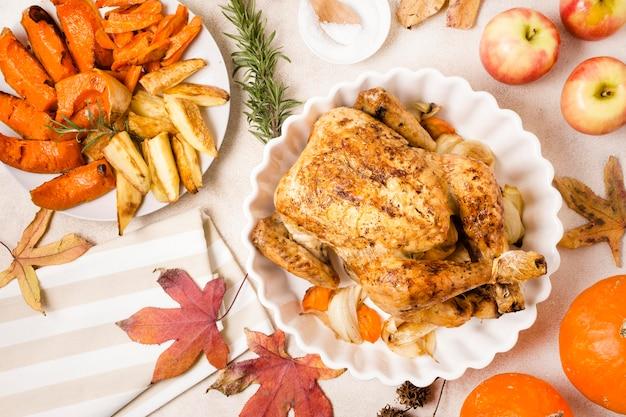 Płaskie układanie dziękczynienia pieczonego kurczaka na talerzu z innymi potrawami