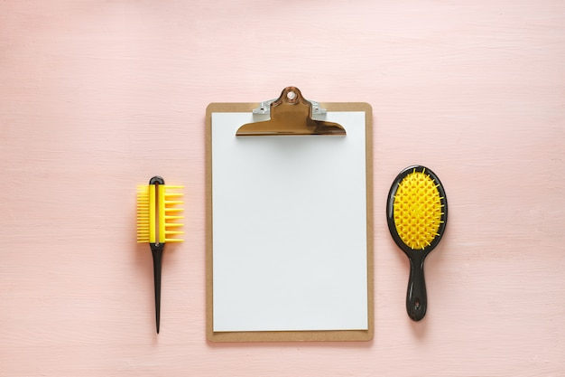 Płaskie układanie grzebieniowych szczotek do włosów z uchwytem do wszystkich typów, lusterkiem kieszonkowym i tabletem składanym, na różowym tle. minimalistyczne kobiece mieszkanie dla blogerów, projektantów, witryn