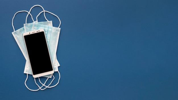 Płaskie układanie masek medycznych ze smartfonem i miejscem na kopię