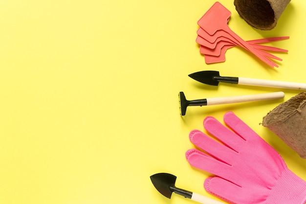 Płaskie układanie materiałów ogrodniczych. narzędzia, garnki torfowe, rękawiczki i talerze do sadzonek na żółtej powierzchni, miejsce na tekst.