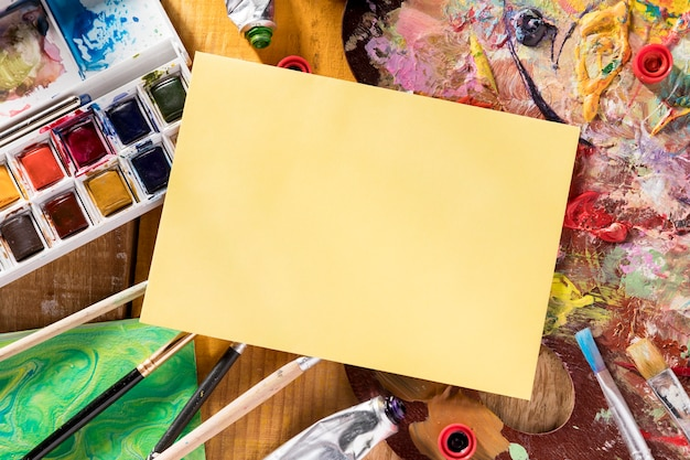 Płaskie układanie palety farb ze szczotkami i papierem