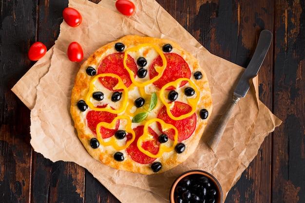 Płaskie układanie pysznej pizzy na drewnianym stole