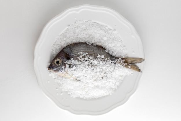 Płaskie układanie ryb na talerzu z solą