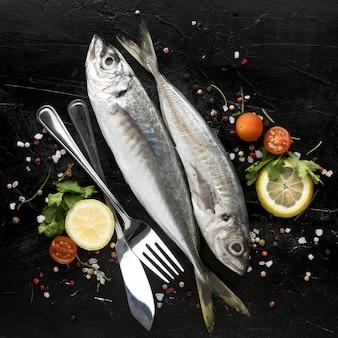 Płaskie układanie ryb z pomidorami i sztućcami