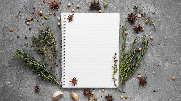 Płaskie układanie składników żywności z notatnikiem i ziołami