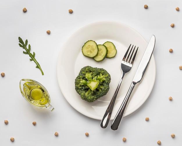 Płaskie układanie świeżych brokułów na talerzu ze sztućcami