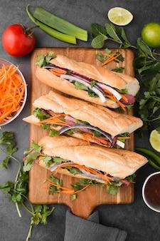 Płaskie układanie świeżych kanapek na desce do krojenia