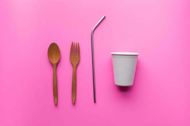 Płaskie układanie trwałych produktów, szkło papierowe, drewniana łyżka i nierdzewna słoma na różowo
