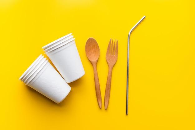 Płaskie układanie trwałych produktów, szkło papierowe, drewniana łyżka i stal nierdzewna na żółto