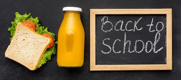Płaskie ukrycie przyborów szkolnych z tablicą i lunchem