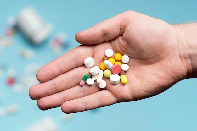 Płaskie ukrycie ręki trzymającej asortyment tabletek
