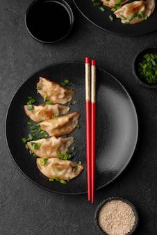 Płaskie ukształtowanie azjatyckiej potrawy na talerzu z pałeczkami