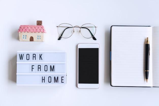 Płaskie ukształtowanie białego biurka z notatnikiem, okularami, smartfonem, modelem domowym i pracą z domowego słowa na lightbox. skopiuj miejsce, widok z góry. kwarantanna, nowa normalna koncepcja domowego biura.