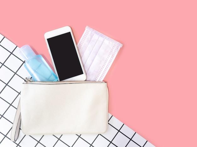 Płaskie ukształtowanie białej kobiety skórzana torba z smartphone, maska chirurgiczna i alkoholowy żel dezynfekujący na różowym tle, widok z góry z miejsca kopiowania tekstu.