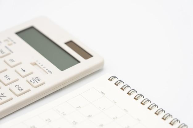 Płaskie ukształtowanie biurka biurkowego z widokiem z góry z kalendarzem, długopisami kalkulatorów i innym biurem