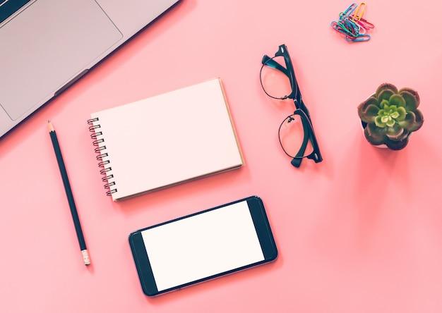Płaskie ukształtowanie biurka roboczego z laptopem, pustym notatnikiem, smartfonem, ołówkiem, papeterią z copyspace