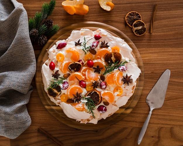 Płaskie ukształtowanie ciasta bezowego ozdobione plasterkami pomarańczy i dzikiej róży
