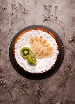 Płaskie ukształtowanie ciasta z plasterkami banana i kiwi