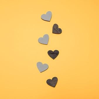 Płaskie ukształtowanie czarno-szare serca w kolejce na żółtym jasnym tle