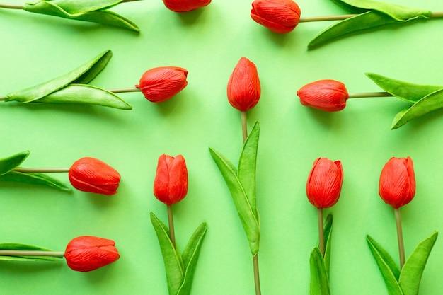 Płaskie ukształtowanie czerwonych tulipanów na zielonym tle, widok z góry.