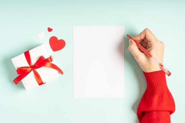 Płaskie ukształtowanie dłoni kobiet z pustym listem i prezentem walentynkowym.