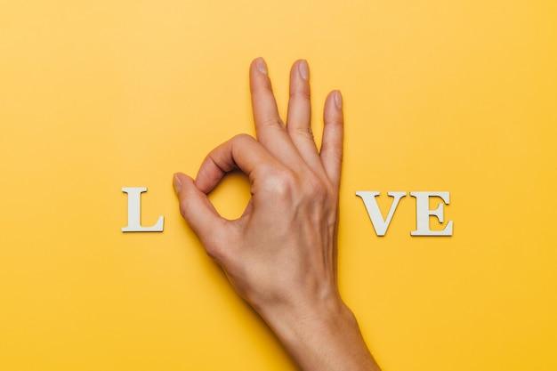 Płaskie ukształtowanie dłoni kobiety jako część słowa miłość.