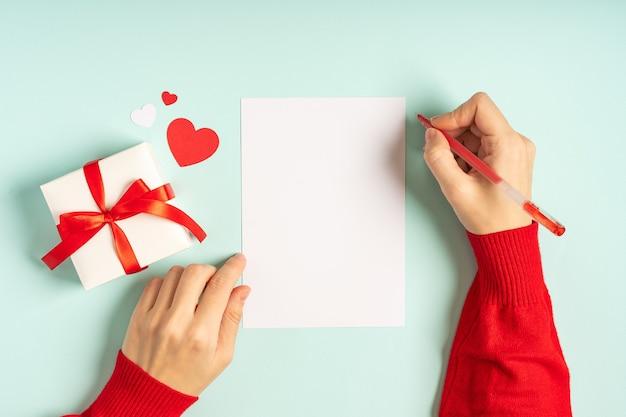 Płaskie ukształtowanie dłoni kobiety z pustą kartkę z życzeniami i prezent walentynkowy.