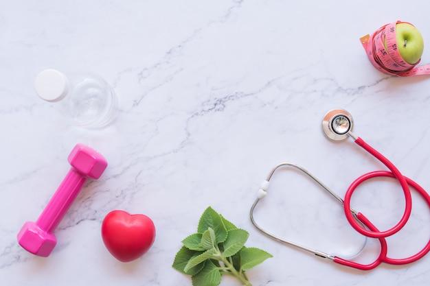 Płaskie ukształtowanie dobrej zdrowej koncepcji, różowy hantle z czerwonym sercem i stetoskop i zielone jabłko na białym tle marmuru