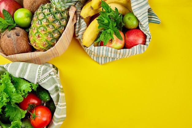 Płaskie ukształtowanie ekologicznych bawełnianych toreb na zakupy spożywcze z ekologicznymi owocami i warzywami