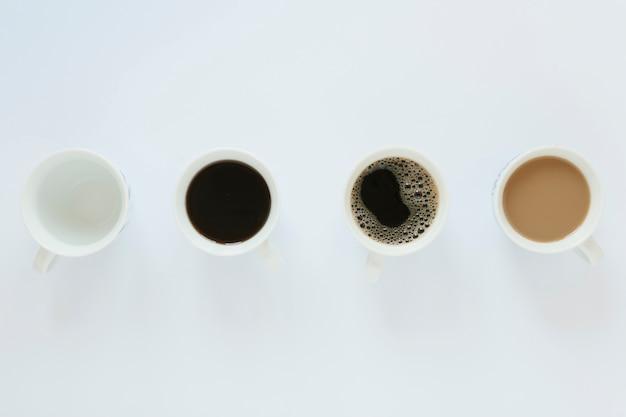 Płaskie ukształtowanie filiżanek kawy na białym stole