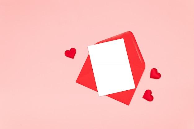 Płaskie ukształtowanie koncepcji literowania miłości z czerwonym sercem kształty i pustą papierową czarną kopertę i arkusz papieru na różowym stole
