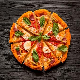 Płaskie ukształtowanie koncepcji pysznej pizzy na drewnianym stole