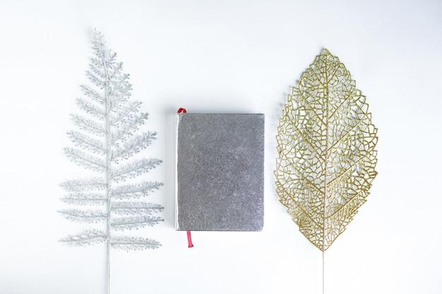 Płaskie ukształtowanie koranu między srebrnymi i złotymi liśćmi na białym tle